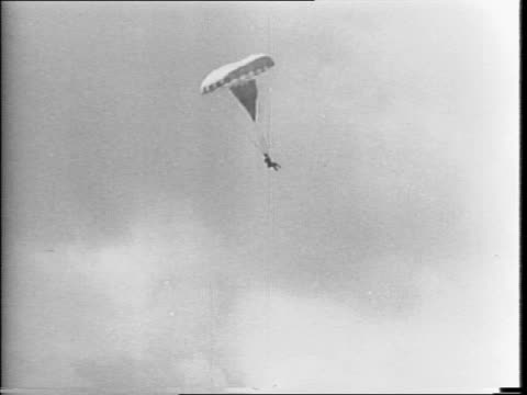 vidéos et rushes de men holding a volfair parachute with cameramen nearby in an open field / men carrying a test dummy attached to a parachute to a plane / pilot trying... - parachute