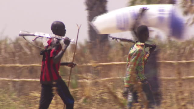 Men holding assault rifles walking in Leer County South Sudan