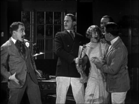 B/W 1926 men holding back screaming woman as man rushes towards her / feature