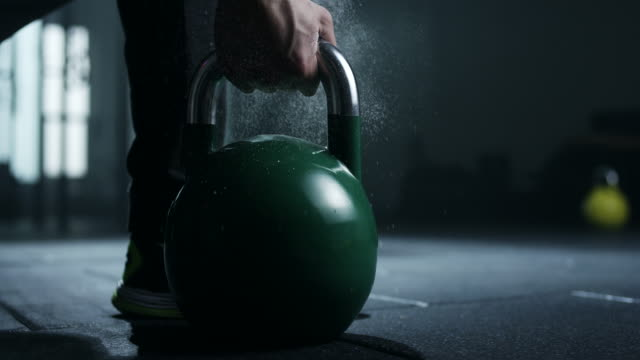 Men holding kettlebell in gym