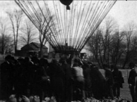 b/w 1906 men holding onto hot air balloon / it lifts off / pittsfield, massachusetts / newsreel - 1906 stock-videos und b-roll-filmmaterial