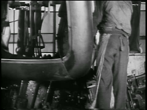 b/w 1932 2 men holding onto rear part of car body in ford car factory / industrial - 1932 stock videos & royalty-free footage