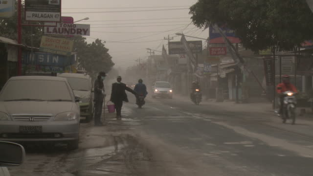 men hose down city street covered in volcanic ash from merapi; central java, indonesia. 30 october 2010 / audio - indonesia street stock videos & royalty-free footage