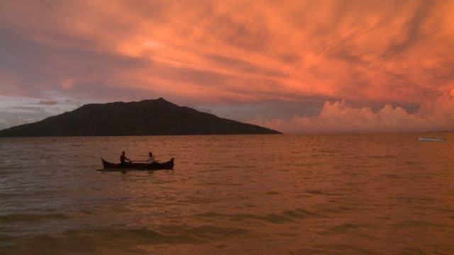 men in a boat paddle toward shore at sunset. available in hd. - madagaskar stock-videos und b-roll-filmmaterial