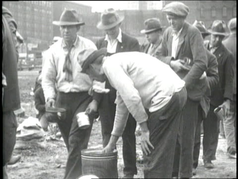 men in a shanty town stand in line for soup and do their laundry - 1930 stock-videos und b-roll-filmmaterial