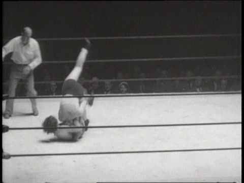 Men in an audience watch intently as two women wrestle in a ring