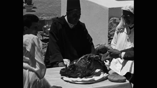 men in arabic dress having meat at table outside - food and drink stock videos & royalty-free footage