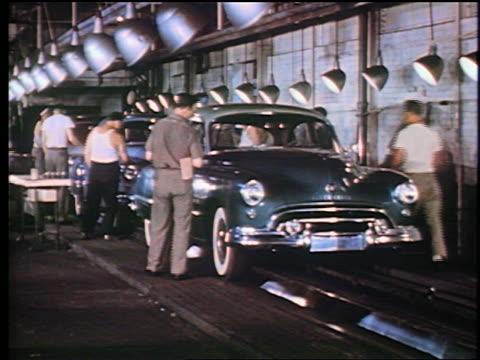 vídeos de stock, filmes e b-roll de 1947 men in assembly line inspect completed 1948 oldsmobiles / man puts sticker on windshield - vintage car
