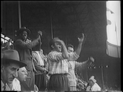 vídeos de stock, filmes e b-roll de b/w 1951 men in audience cheering shouting clapping at playoff game / polo grounds / nyc - 1951