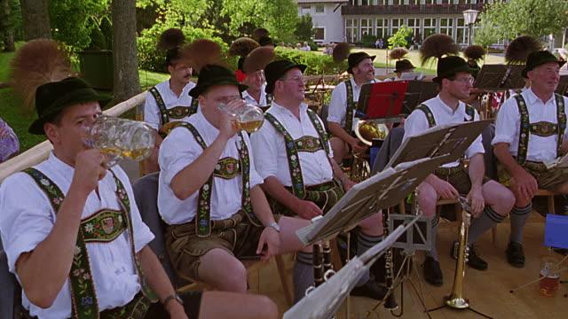 vidéos et rushes de men in band wearing german costumes + drinking mugs of beer on stage in park / bad kohlgrub, bavaria - bavière