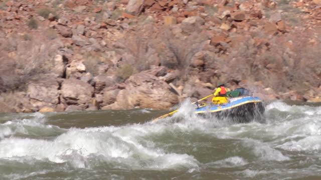 WS PAN Men in blue raft moving on rapid / Grand Canyon, Arizona, USA
