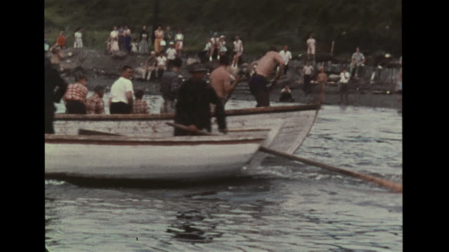 men in boats beating water to encouraging lost pilot whales to move closer to shore, people standing on beach watching. men catching & helping,... - cetaceo video stock e b–roll