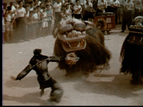 1957 MONTAGE Men in ceremonial Chinese lion costumes dance mock fight w/ warrior while crowd watches. Drummer beats large drum w/ sticks + feet / Singapore / AUDIO