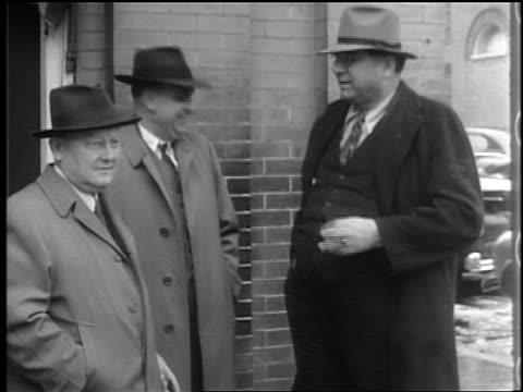 b/w 1944 3 men in coats + hats stand + talk on street corner / lexington, nc / documentary - オーバーコート点の映像素材/bロール