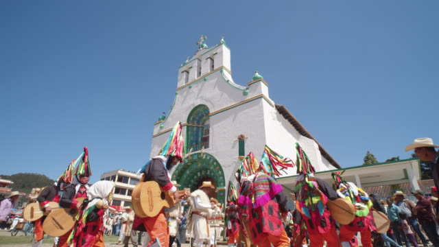 vídeos de stock e filmes b-roll de men in colorful traditional costumes dancing and playing guitarra chamula in front of the church of san juan chamula during the traditional syncretic town festival - maia