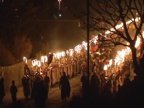 men in costumes holds flamming torches during a parade for the up helly aa festival - galeere stock-videos und b-roll-filmmaterial