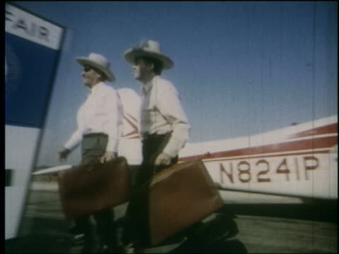 pan 2 men in cowboy hats with luggage walk from airplane past world's fair sign / ny - 1964年点の映像素材/bロール