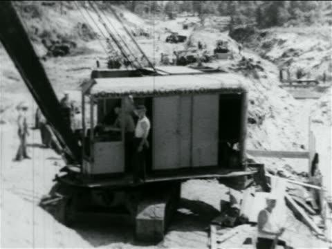 stockvideo's en b-roll-footage met b/w 1934 men in crane turning in wpa sewage construction project / documentary - bouwvoertuig