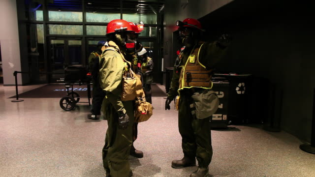 MEDIUM PAN men in gas masks and hardhats talk in lobby then descend stairs in Barclays Center - members of US Marines and FDNY take part in joint drill aimed at strenghting preparedness for chemical and biological attacks at Barclays Center