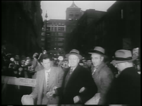 men in hats escorting george metesky on nyc street / newsreel - 1957 stock-videos und b-roll-filmmaterial