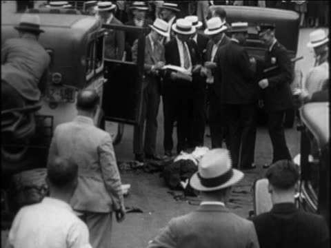 b/w 1921 men in hats police standing by dead body on city street / prohibition / documentary - 1921 stock videos & royalty-free footage