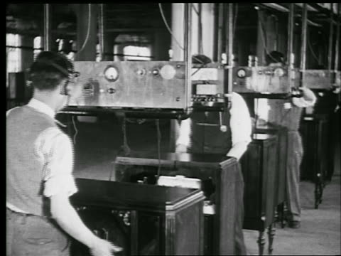 B/W 1929 men in headsets testing radios in factory / Philadelphia / industrial