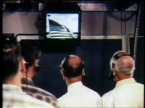 VIEW men in headsets watching American flag on TV / first satellite broadcast