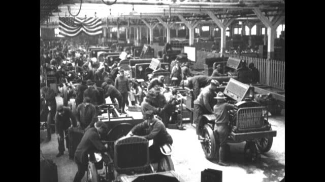 vídeos y material grabado en eventos de stock de men in liberty truck factory building trucks / soldiers help lower motor into truck / convoy liberty trucks on road - 1910