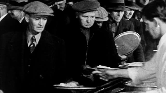 stockvideo's en b-roll-footage met men in line waiting for soup and bread during the great depression / men being served meals / soup being ladled into bucket / woman spooning food out... - 1933