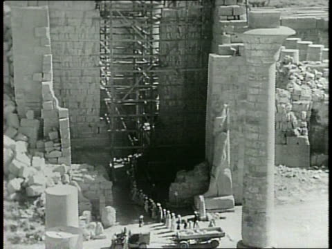 men in long robes walk across scaffolding over a work site / a line of men work on the monument from a distance using the large scaffolding up the... - pharaoh stock videos & royalty-free footage
