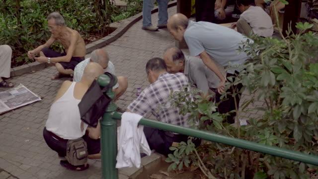 Men in Macau park playing cards