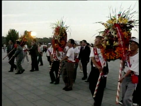 men in mourning carry large red wreaths to statue of kim il sung following his death pyongyang; aug 94 - 月経前緊張症候群点の映像素材/bロール