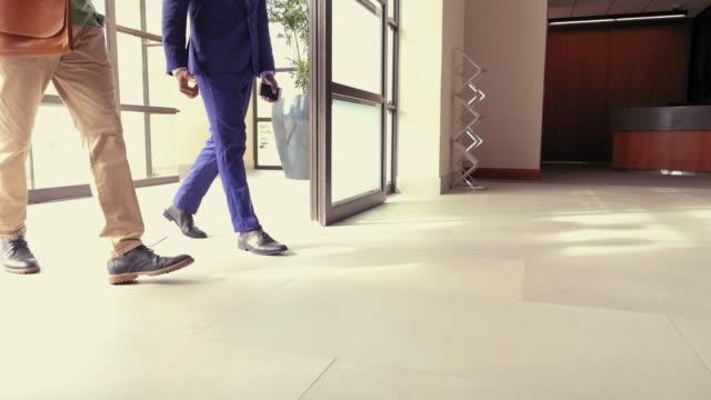 vídeos de stock, filmes e b-roll de men in office lobby - chegada