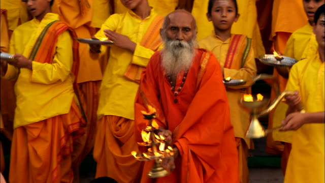 vidéos et rushes de men in orange robes wave around candles during a religious ceremony. available in hd. - fidèle religieux