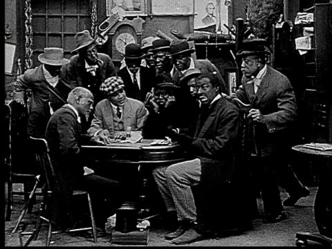 vidéos et rushes de 1916 b&w ms men in poker game hiding cards and chips after man enters and speaks to them/ man standing up and reading paper  - poker