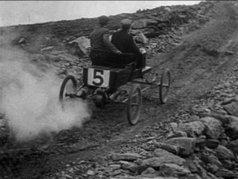 VIEW 2 men in race car going up steep Pike's Peak Colorado / documentary