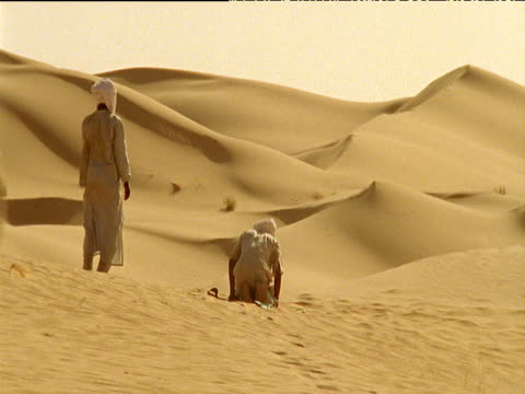 vidéos et rushes de men in robes kneel down and pray legs of camel train pass in foreground sahara desert - coiffe traditionnelle