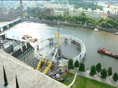 men in safety harnesses work on rim of london eye while still horizontal; jul 99 - ミレニアムホイール点の映像素材/bロール