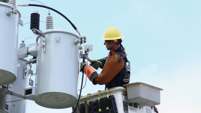 ms la pan men in saftey gear attaching power line to transformer box / oyster, virginia, usa - stromleitung stock-videos und b-roll-filmmaterial