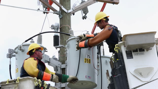 ms la pan men in saftey gear attaching power line to transformer box / oyster, virginia, usa - elettricità video stock e b–roll