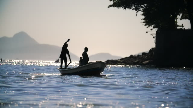 men in small fishing boat wave a signal and steer for shore in slow motion - 手を振る点の映像素材/bロール