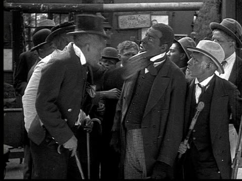 1916 B&W MS men in suits having argument and raising walking sticks at each other