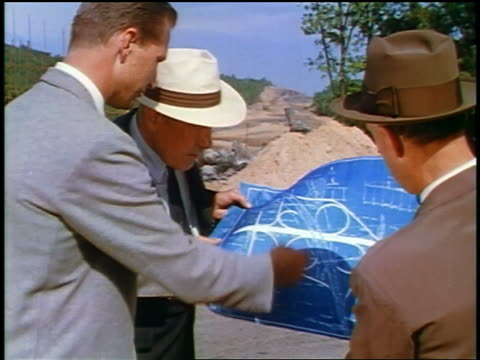 1957 rear view 3 men in suits looking at blueprints at construction site - 1957 stock-videos und b-roll-filmmaterial