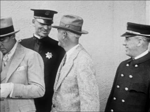 vidéos et rushes de pan men in suits police standing with rudolph valentino in hat / newsreel - 1926