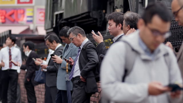 men in suits smoke and use smartphones, tokyo - fare una pausa video stock e b–roll