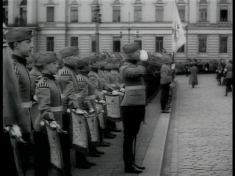 Men in suits walking in parade Soldiers standing at edge of street President of the Republic of Finland Kyosti Kallio walking w/ soldiers Decorated...
