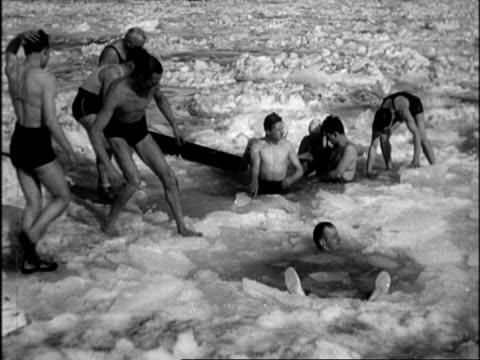 vídeos y material grabado en eventos de stock de men in swimsuits bathing in ice hole / senior men sitting in ice hole kicking / man doing headstand in ice hole as others look on. polar bear... - 1934