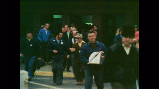 1978 Men in their civilian clothes exit the factory as voiceover explains workplace pollution can be transferred from workers to their families