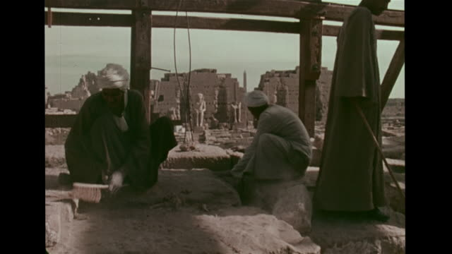 men in traditional clothing dusting, cleaning stones in temple ruin, egyptian statues bg, scaffolding, people digging, excavating. slightly faded,... - archaeology stock videos & royalty-free footage