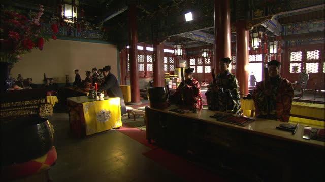 stockvideo's en b-roll-footage met men in traditional clothing worship behind tables at baiyun guan in beijing, china. - men